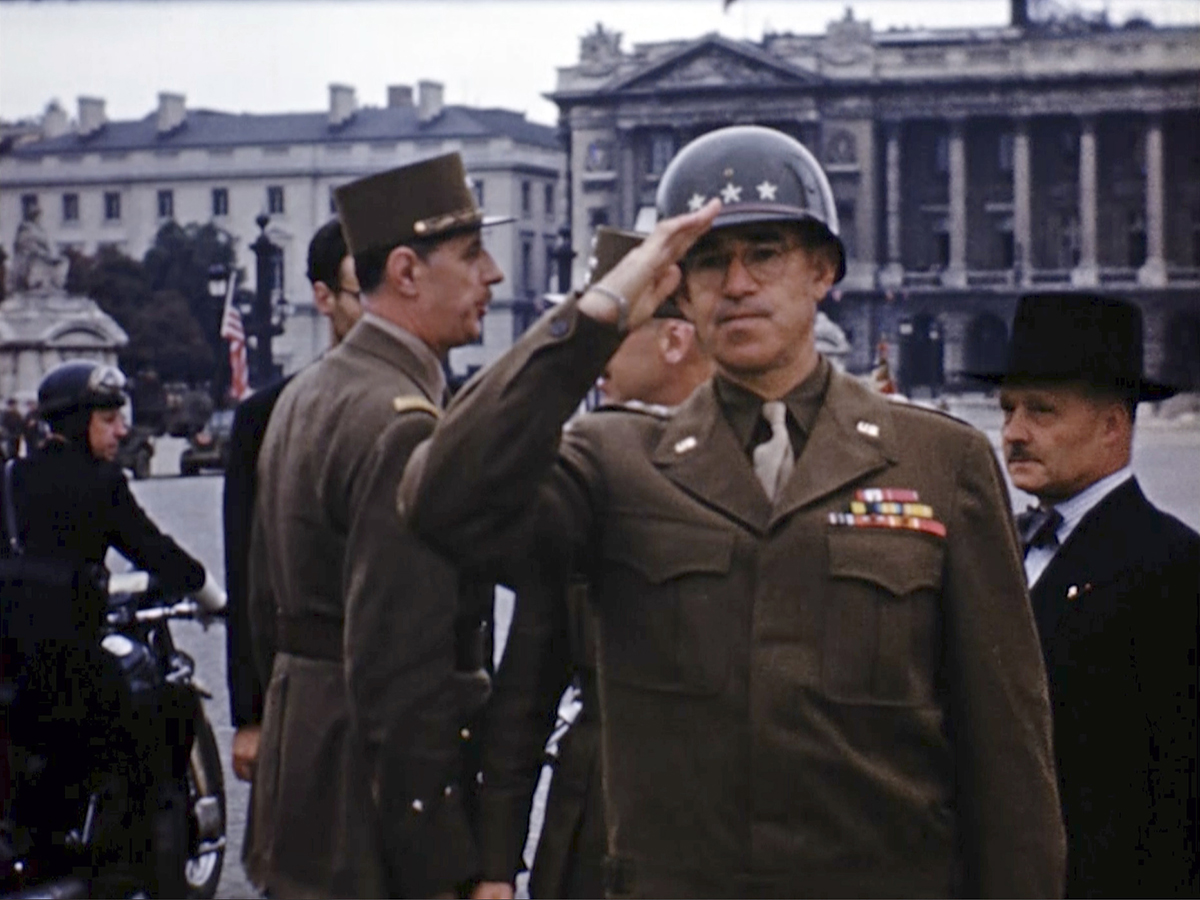 U.S. Gen. Omar Bradley salutes as Charles de Gaulle, background left, speaks before for a military parade down the Champs-Elysees after the liberation of Paris. Seventy-five years later, surprising color images of the D-Day invasion and aftermath bring an immediacy to wartime memories. They were filmed by Hollywood director George Stevens and rediscovered years after his death. (War Footage From the George Stevens Collection at the Library of Congress via AP)
