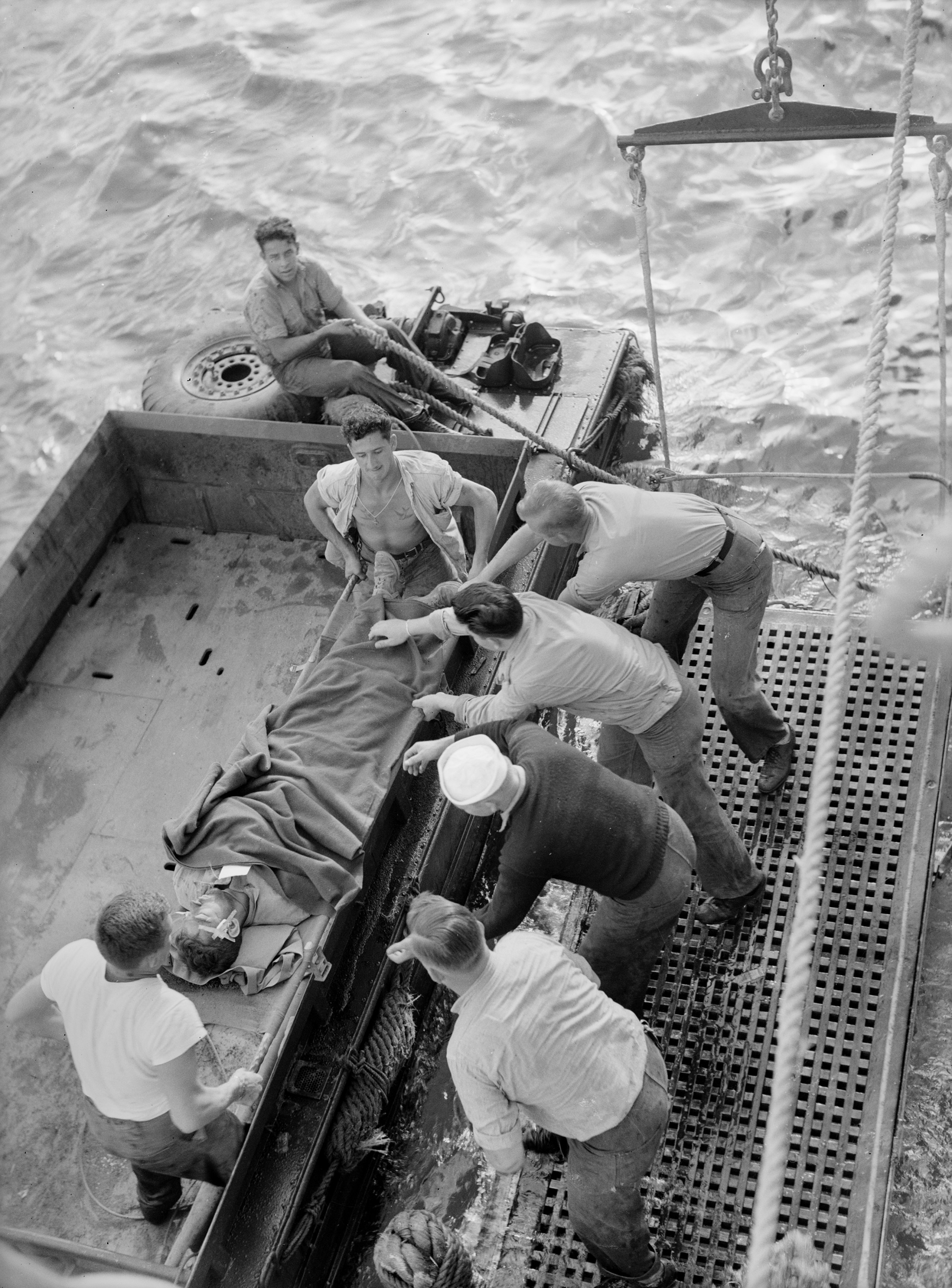 A boat crew off-loads a wounded man onto a hospital ship, 1945. (Wisconsin Historical Images 58816)