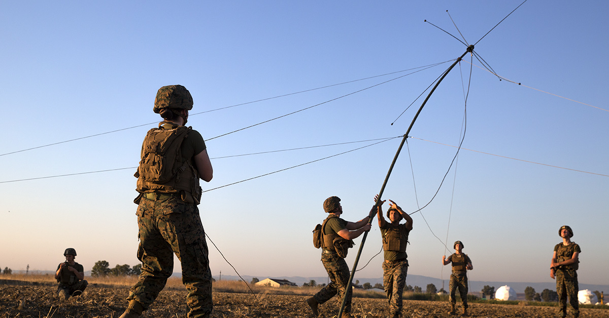 Marines assigned to Special Purpose Marine Air-Ground Task Force-Crisis Africa, Logistics Combat Element 18.2, raise a radio antenna, at Naval Air Station Sigonella, July 11, 2018. The Marines set up and tested an OE-254 radio antenna and practiced proper radio etiquette when using a PRC 152 radio over very high frequencies. The training was meant to ensure that all Marines were adequately cross-trained in basic communication skills and prepared to use the knowledge on the Battle Skills Test. (Cpl. Taylor W. Cooper/ Marines)