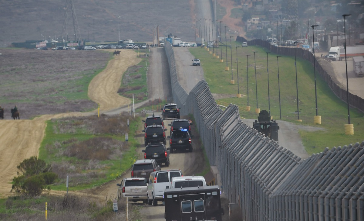 A motorcade carrying U.S. President Donald Trump drives past a U.S.-Mexico border fence as he heads for an inspection of border wall prototypes in San Diego, Calif., on March 13, 2018. (Mandel Ngan/AFP via Getty Images)