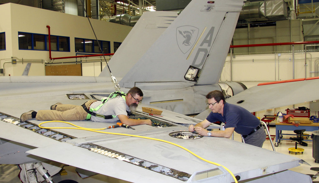 In this Wednesday, April 25, 2018, photo, flight operations mechanic Shawn Edwards, left, removes the left-hand flap shroud from the wing of a 13-year-old F/A-18 Super Hornet in St. Louis. This fighter aircraft, at the end of its original lifespan, was used by the U.S. Navy Gladiators Strike Fighter Squadron based out of Virginia Beach, Va. It is the first Super Hornet of many, set to undergo updates and maintenance to keep it in the fleet for another dozen years. (Ted Shaffrey/AP)